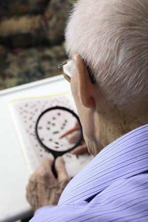 year profile: A elderly man sitting doing crosswords hobby
