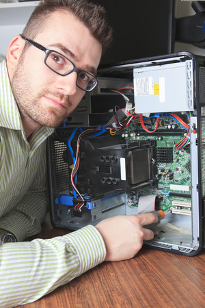 A happy worker technician at work with computer. photo