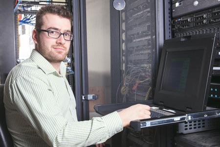 professionnel: Un technicien de travailleur heureux au travail avec l'ordinateur. Banque d'images