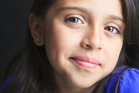 ambiguous: A Columbian Little Girl Fun Look in front of a black background
