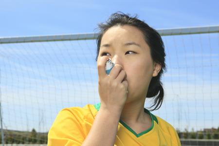 asma: Retrato de la muchacha asi�tica joven con bal�n de f�tbol.