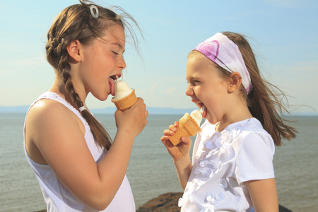 ice cream woman: Sister eating ice-cream in front of ocean Stock Photo