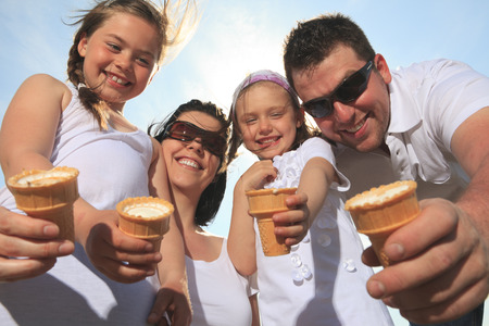 ice cream woman: family eating ice-cream in front of ocean Stock Photo