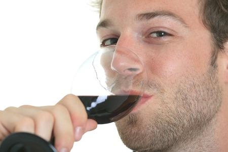 25 30 years: Casual young man holding glass of wine, smiling. Isolated on white.