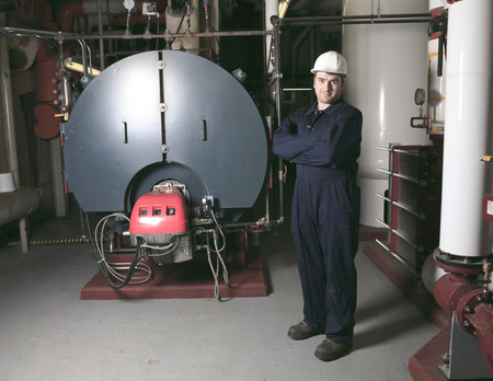 condensing: maintenance engineer checking technical data of heating system equipment in a boiler room