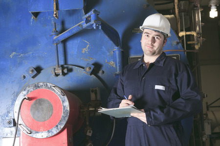 hause: maintenance engineer checking technical data of heating system equipment in a boiler room
