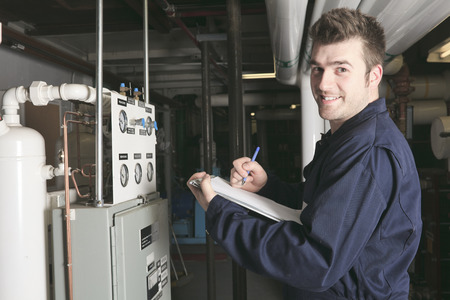 maintenance engineer: maintenance engineer checking technical data of heating system equipment in a boiler room