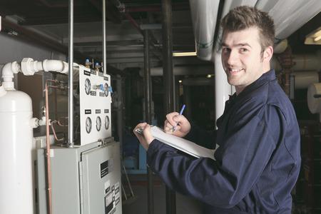 onderhoudsmonteur controleren van technische gegevens van de verwarmingsinstallatie apparatuur in een stookruimte