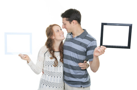 looking through frame: Happy couple in frame. Beautiful young couple looking through a picture frame and smiling while isolated on white
