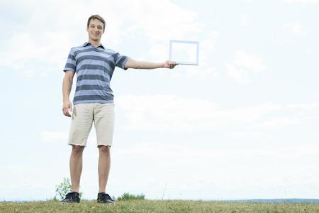 A men outside having fun with photo frame photo