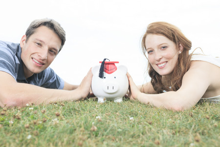 piggybank: money, outside, finance and relationships concept - smiling couple with piggybank Stock Photo