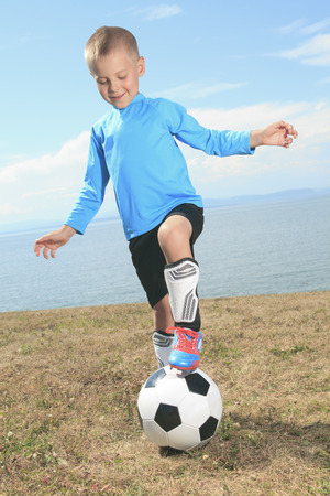 young boy smiling: the boy with a soccer ball outside.