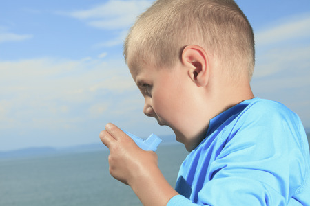A young sport boy using inhaler outside Stock Photo
