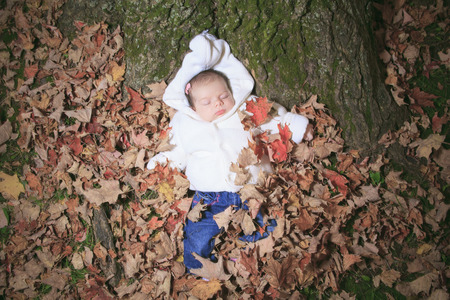 A Newborn baby laying on the leaf of a autumn park
