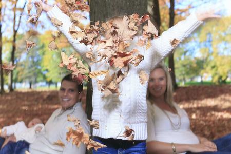 admire: A Family enjoying golden leaves in autumn park
