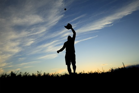 A man silhouetted by the sunset is just beginning catch ball with glove photo