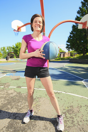 30 years old woman: Girl ready to play basketball on the playground