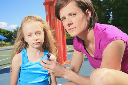 asthmatic: mother using inhaler with her asthmatic daughter Stock Photo