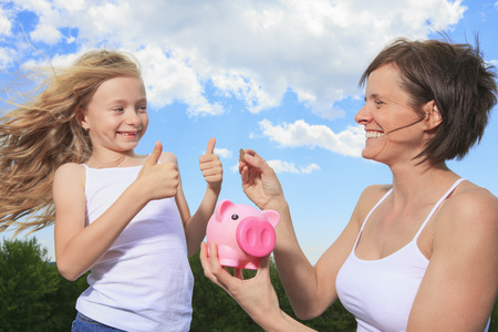 A Piggy Bank and Coin holding by a little girl photo