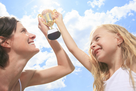 academic achievement: A Happy mother and daughter holding a trophy high up