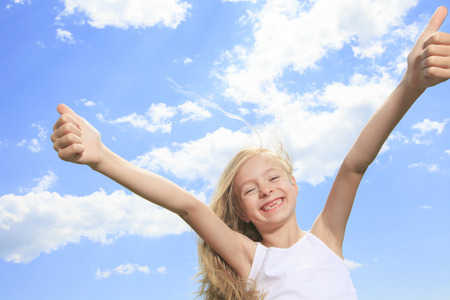 pre approval: A smiling little girl in white blank t-shirt showing thumbs up over blue sky