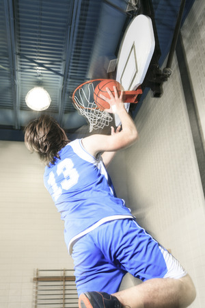 A teenager basketball player play his favorite sport