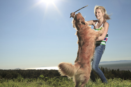 retreiver: Funny girl plays with the dog outside Stock Photo