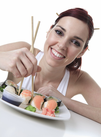 young woman eating a sushi piece against a white