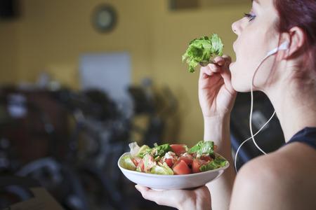 ni�a comiendo: Hermosa mujer joven en el gimnasio comer ensalada Foto de archivo