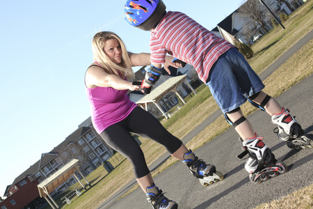 overbalance: Active family - mother and kid having fun, rollerblading outdoor on a sunny summer day