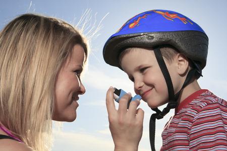 sick boy: A boy having a asthma problem outside.