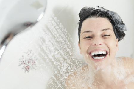 샤워 여자. 욕실에 샤워 행복 웃는 여자 세척 어깨.