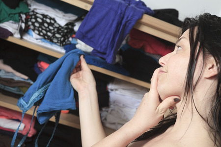 A woman try to choose clothes on her closet photo