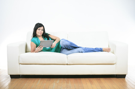 sofa: Young woman using electronic tablet sitting on sofa Stock Photo