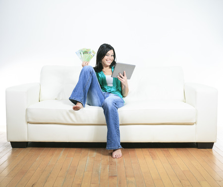 25 to 30 years old: Young woman using electronic tablet sitting on sofa Stock Photo