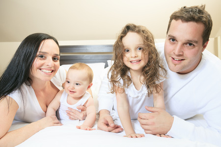 9 months old: Young family resting together in parents bed Stock Photo