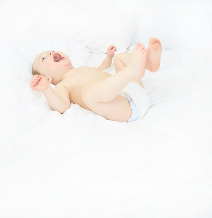 6 9 months: A Baby boy playing on the parent bed