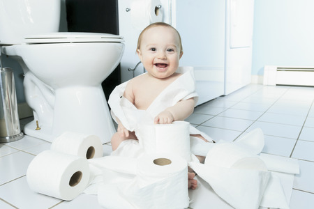 Peuter rippen up wc-papier in de badkamer