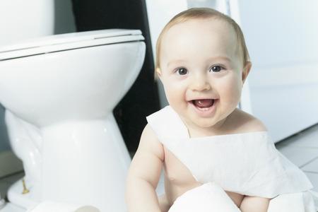 幼児がトイレでトイレット ペーパーをリッピング 写真素材