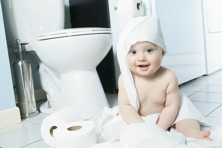 Toddler ripping up toilet paper in bathroom