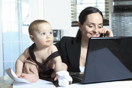 busy mother with her baby in the kitchen table photo