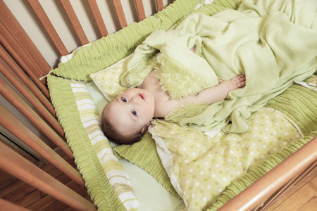 bonnie: Overhead view of cute baby boy lying under blankets in wooden crib or cot.