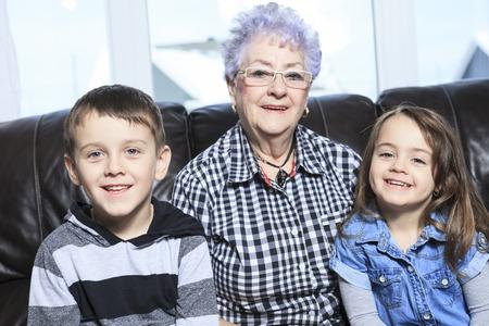 Portrait of smiling multigeneration family spending leisure time together at home Standard-Bild