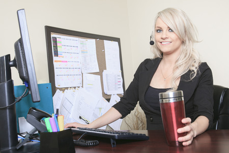 outwork: beautiful young woman sitting at her desk in the workplace