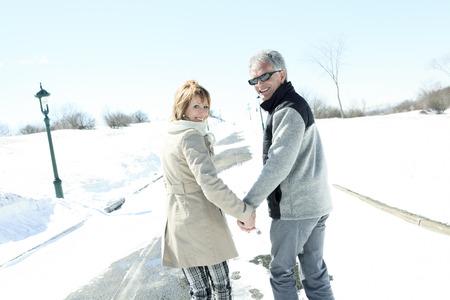 personas abrazadas: Retrato de la feliz pareja senior en temporada de invierno Foto de archivo