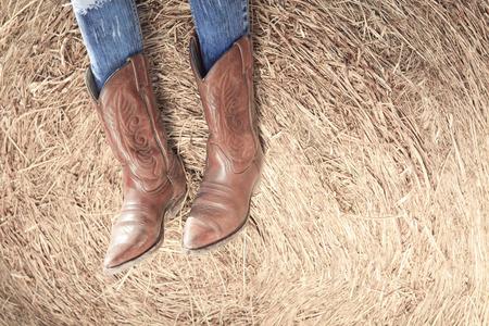 vaqueritas: Imagen de estilo occidental de vaqueras piernas en pantalones vaqueros y botas en la pared desierta Foto de archivo
