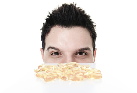 omega3: A young man is eating a omega-3 pill