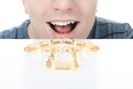 젊은 남자는 오메가 -3 약을 먹고있다 스톡 콘텐츠