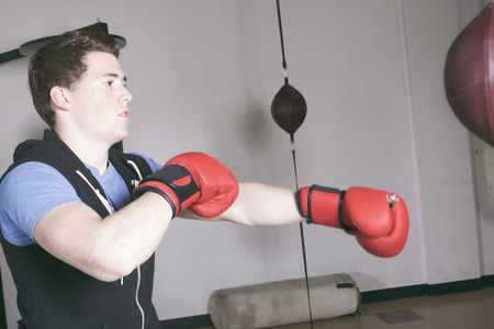 tough: A Boxers doing some training on a punching bag at a gym Stock Photo