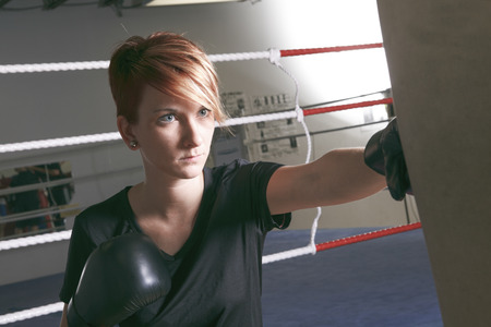 punching: fitness woman doing punching exercises in training place